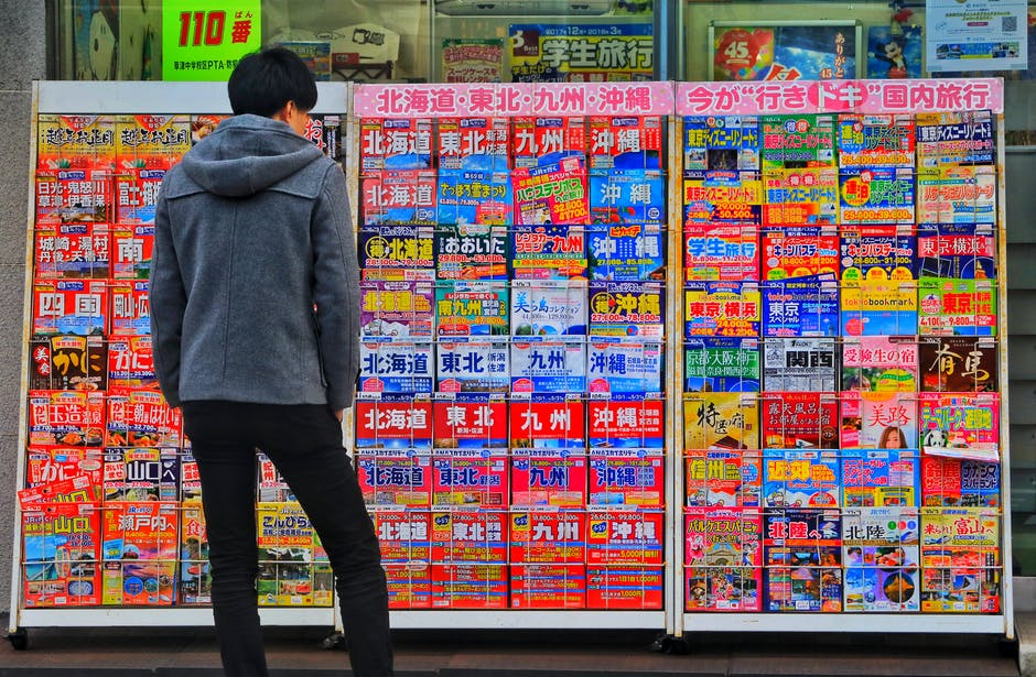 Standing Man Wearing Gray Hoodie in Front of Magazine in Rack