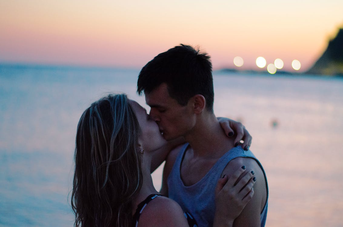 Selective Focus Photography of Couple Kissing on Shore