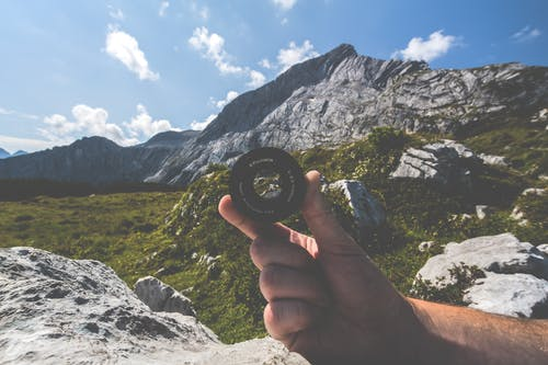 Person Holding Black Camera Lens Near Mountain