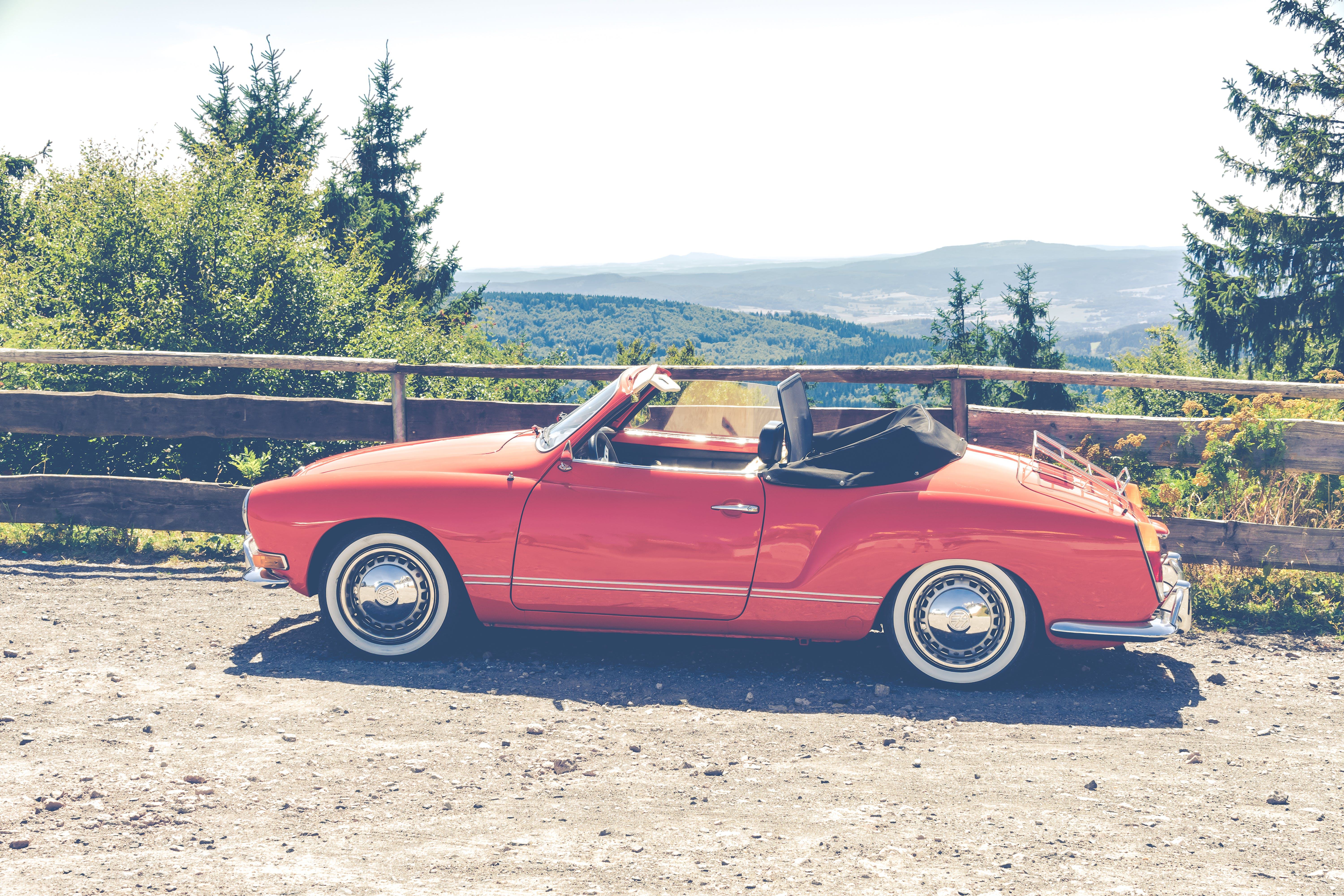 Red Convertible Coupe Parked Near Wooden Fence Overlooking Trees