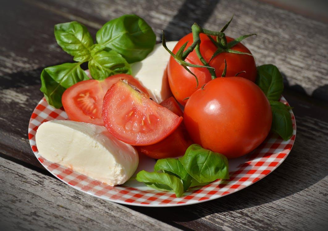 Pomodori E Formaggio Sul Piatto Rosso