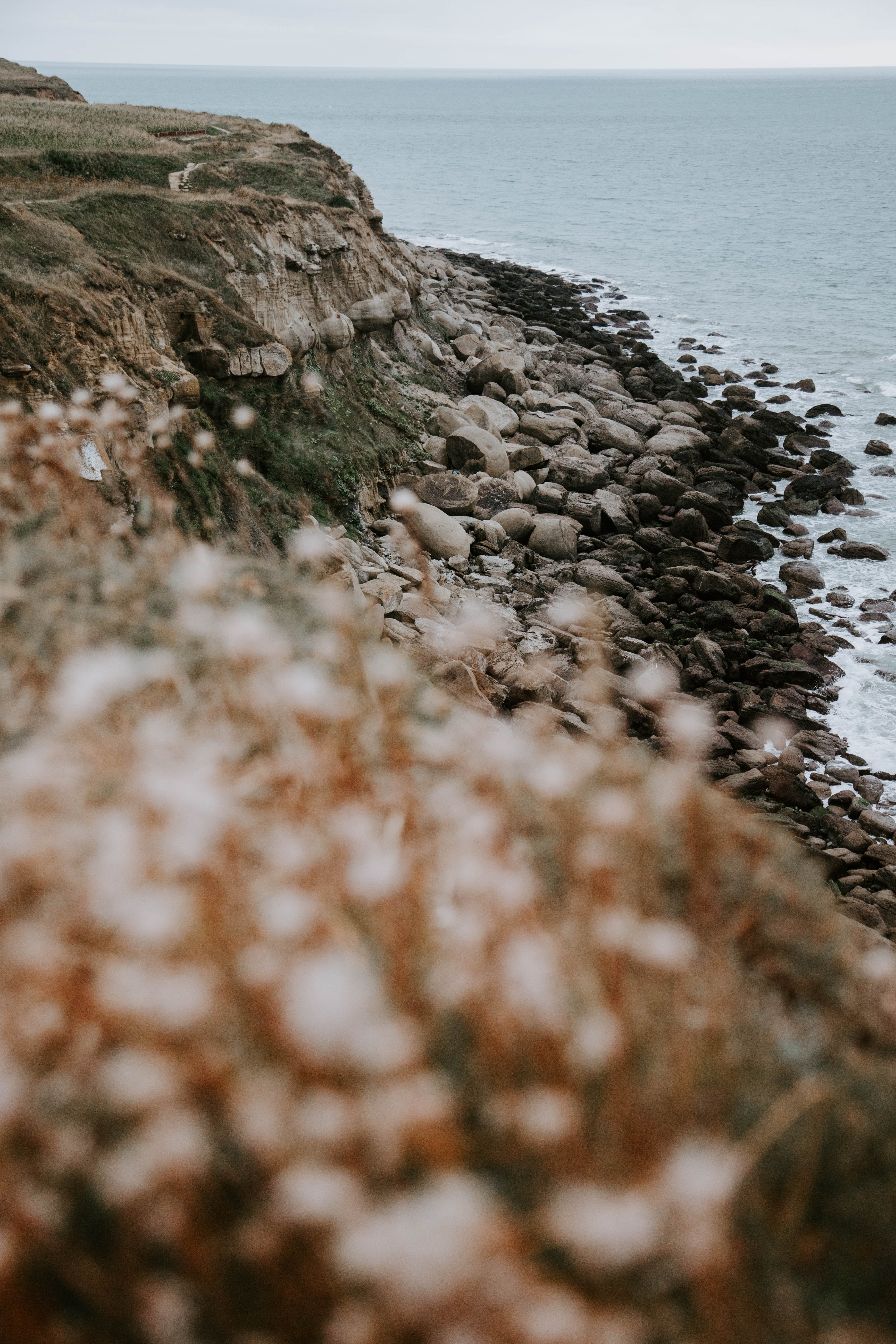 Selective Focus Photography of Seashore With Stones Near Sea