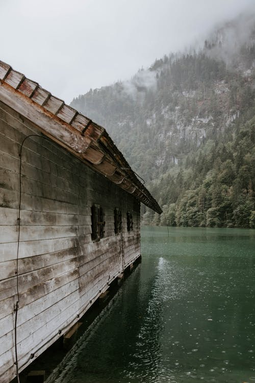 Brown Wooden Cabin Surrounded by Body of Water