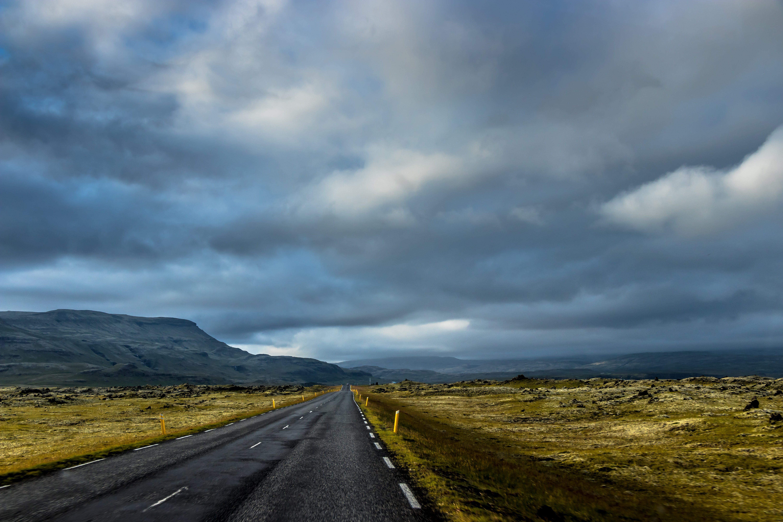 Empty Road in Between Grass Field