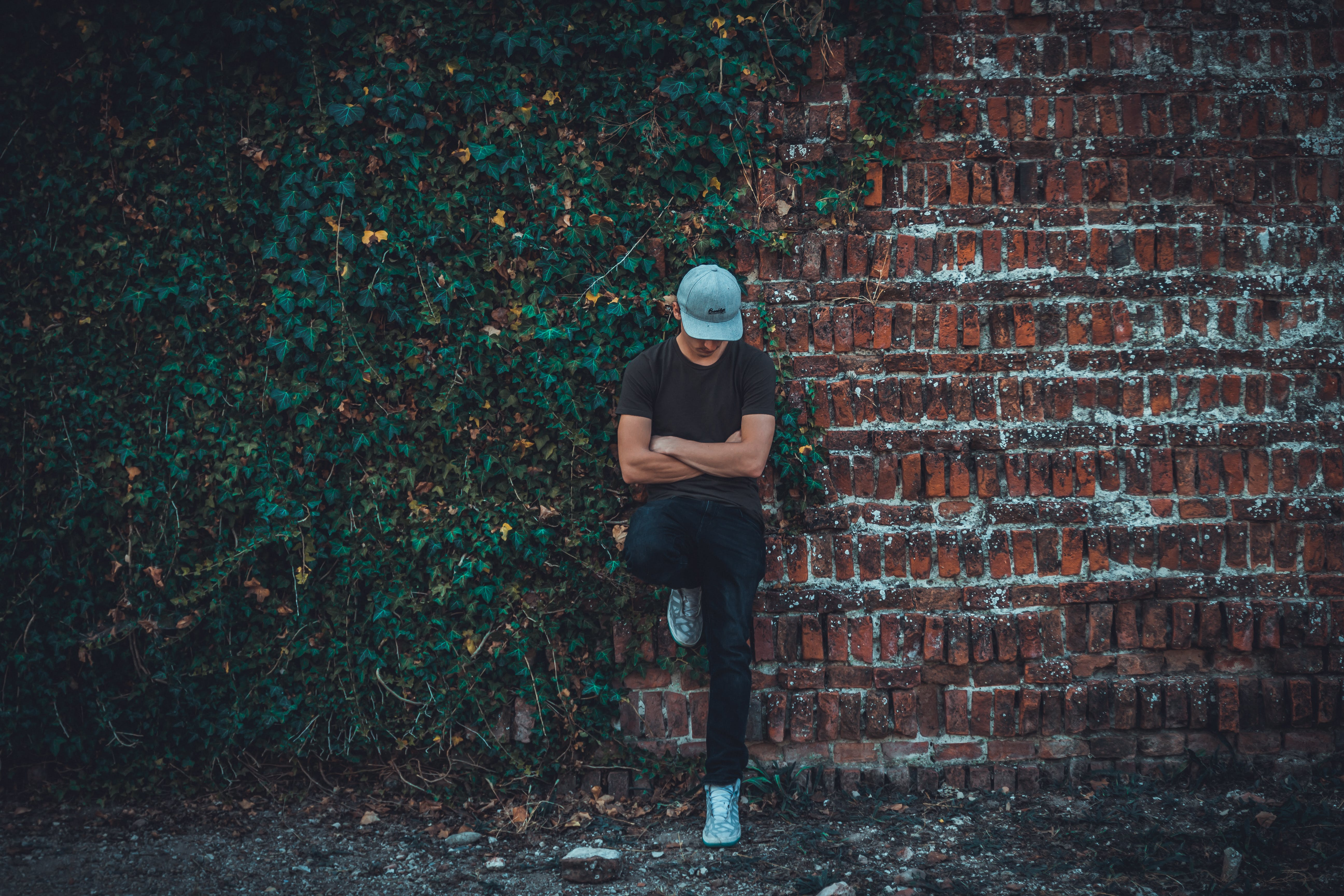 Man Leaning on Brick Wall