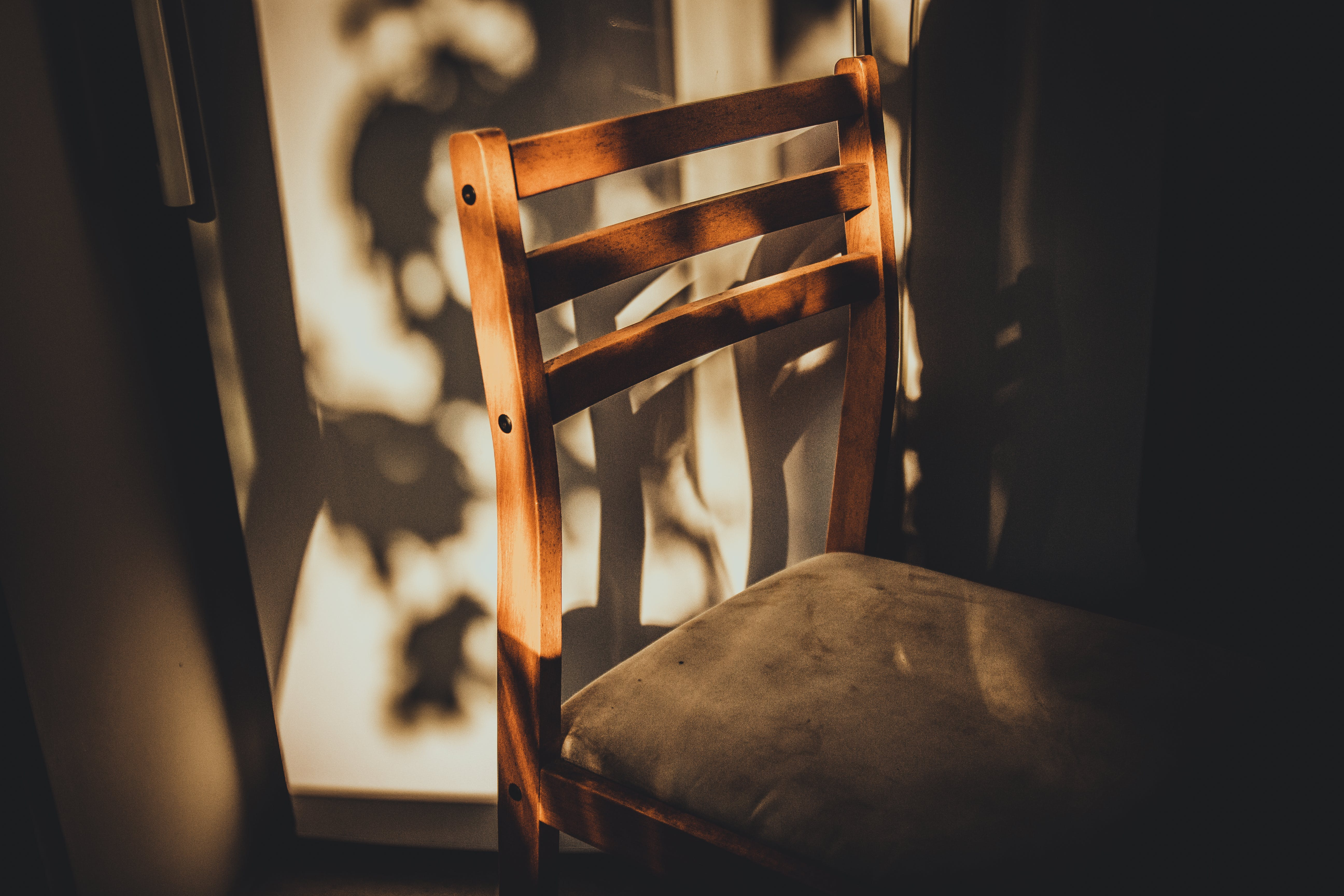 Brown Wooden Chair Beside White Painted Wall