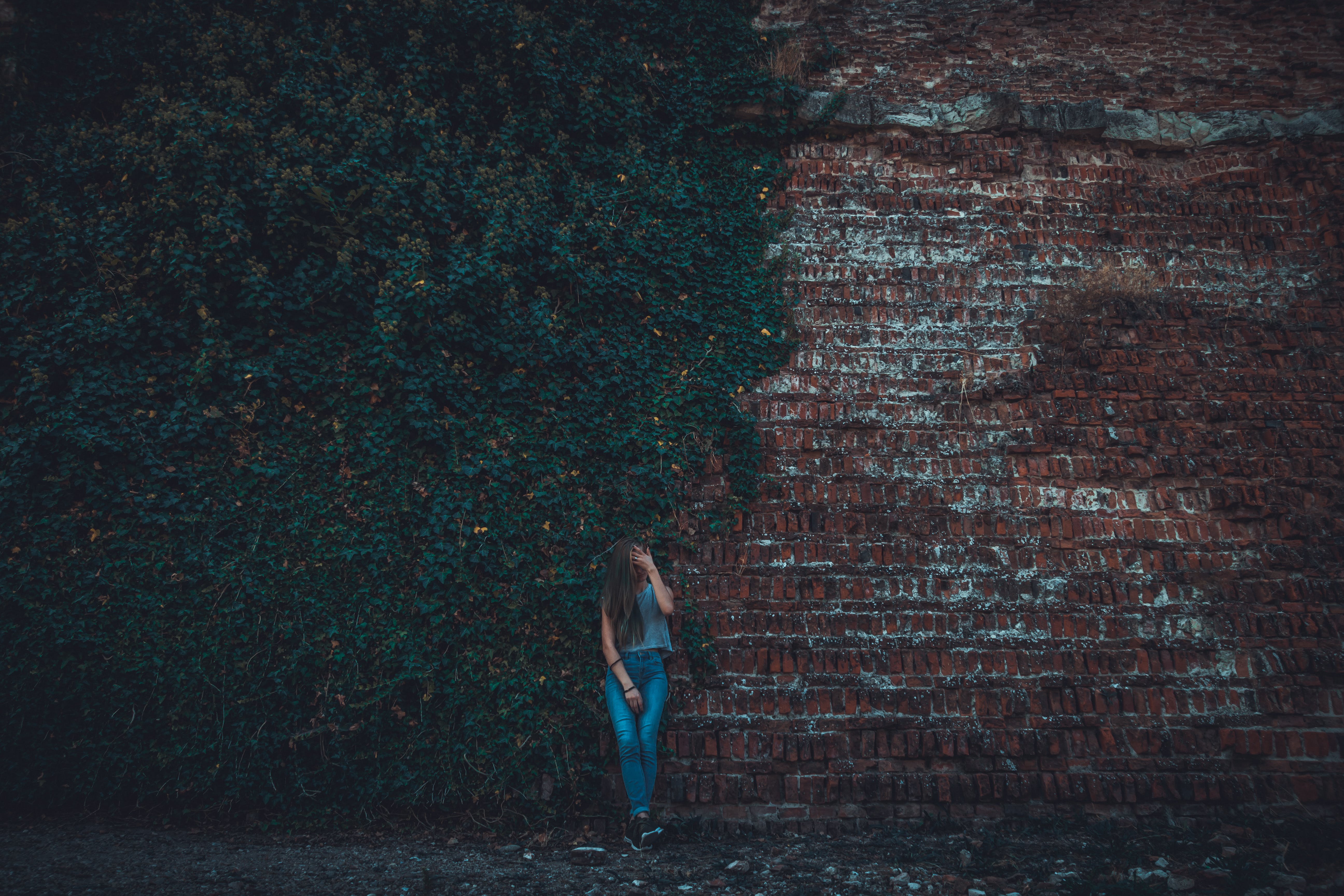Woman Leaning on Brown Stone Wall