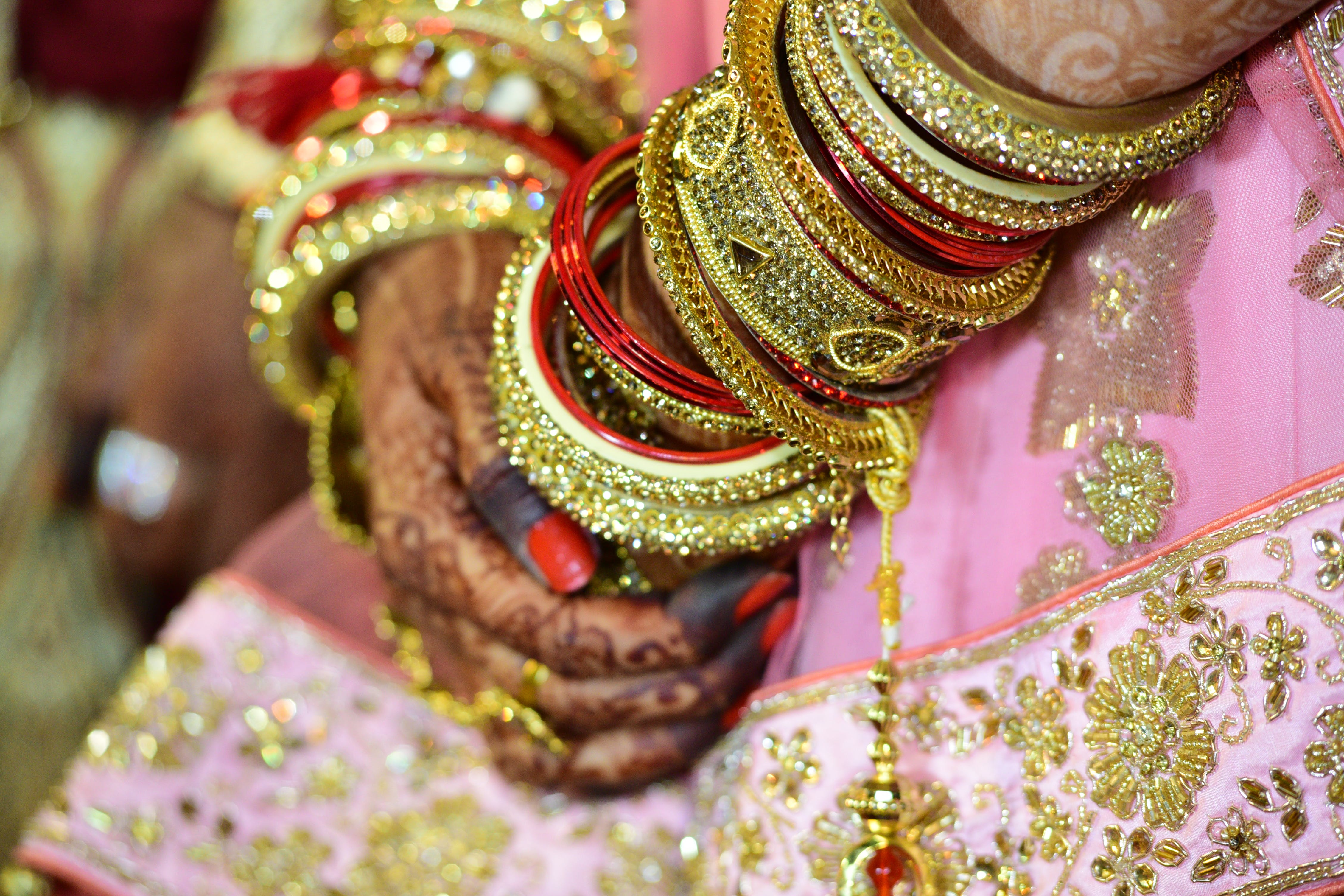 Woman Wearing Gold-colored Bangle and Mehndi