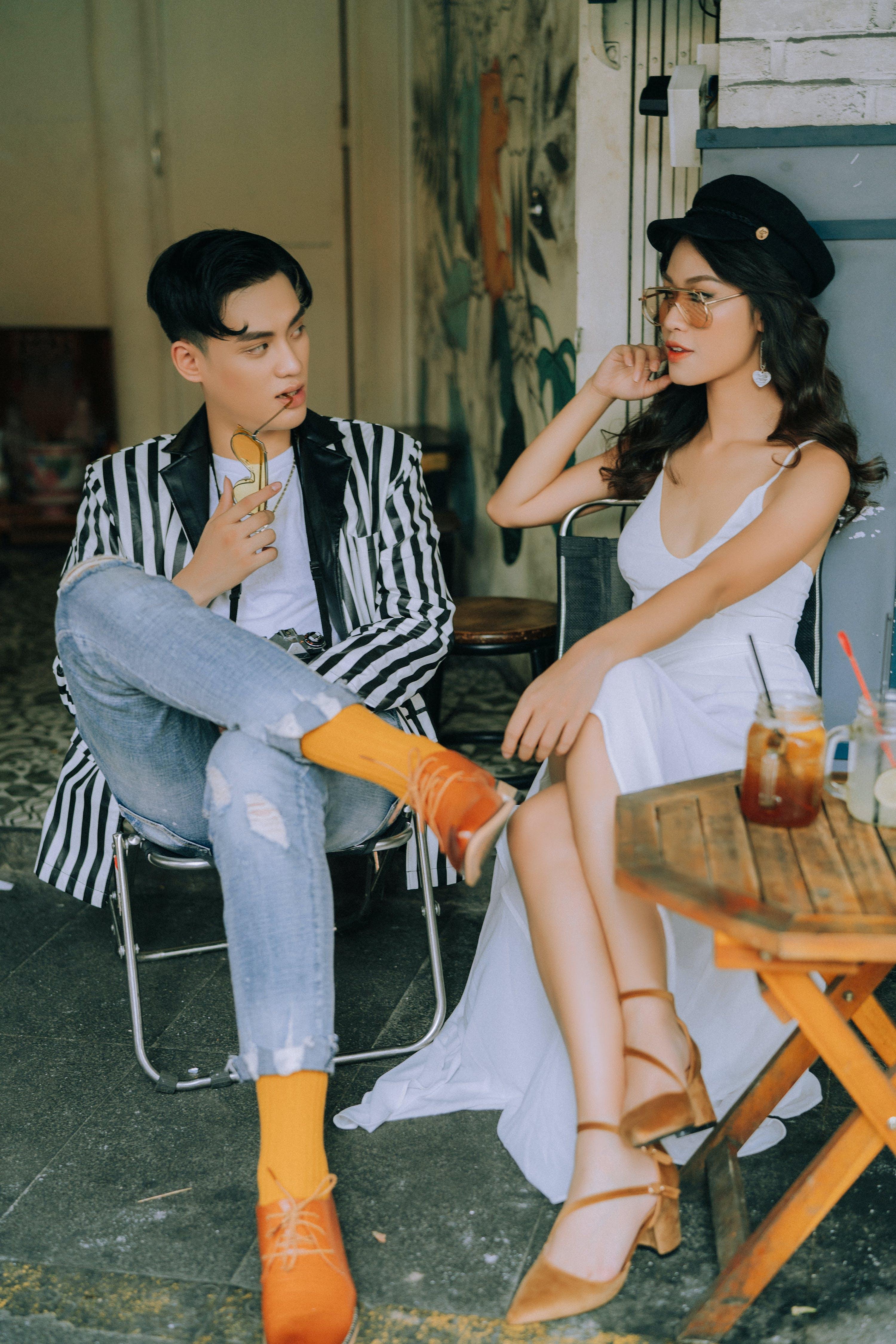 Man Sitting on Folding Chair Beside Woman Sitting Near Table