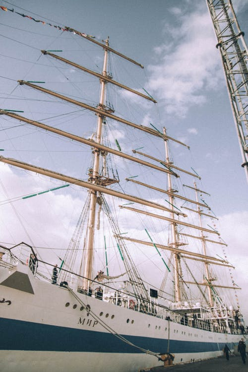 Sailing ship at anchor near pier in cloudy day