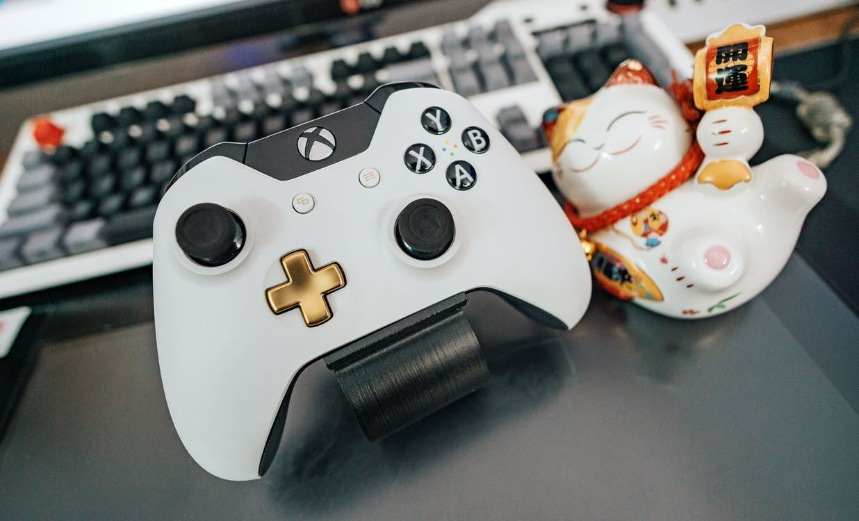 White and Black Xbox One Wireless Controller Beside White and Multicolored Ceramic Cat Figurine on Black Surface