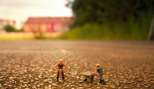 Selective Focus Photography of Two Men Builder Figurines