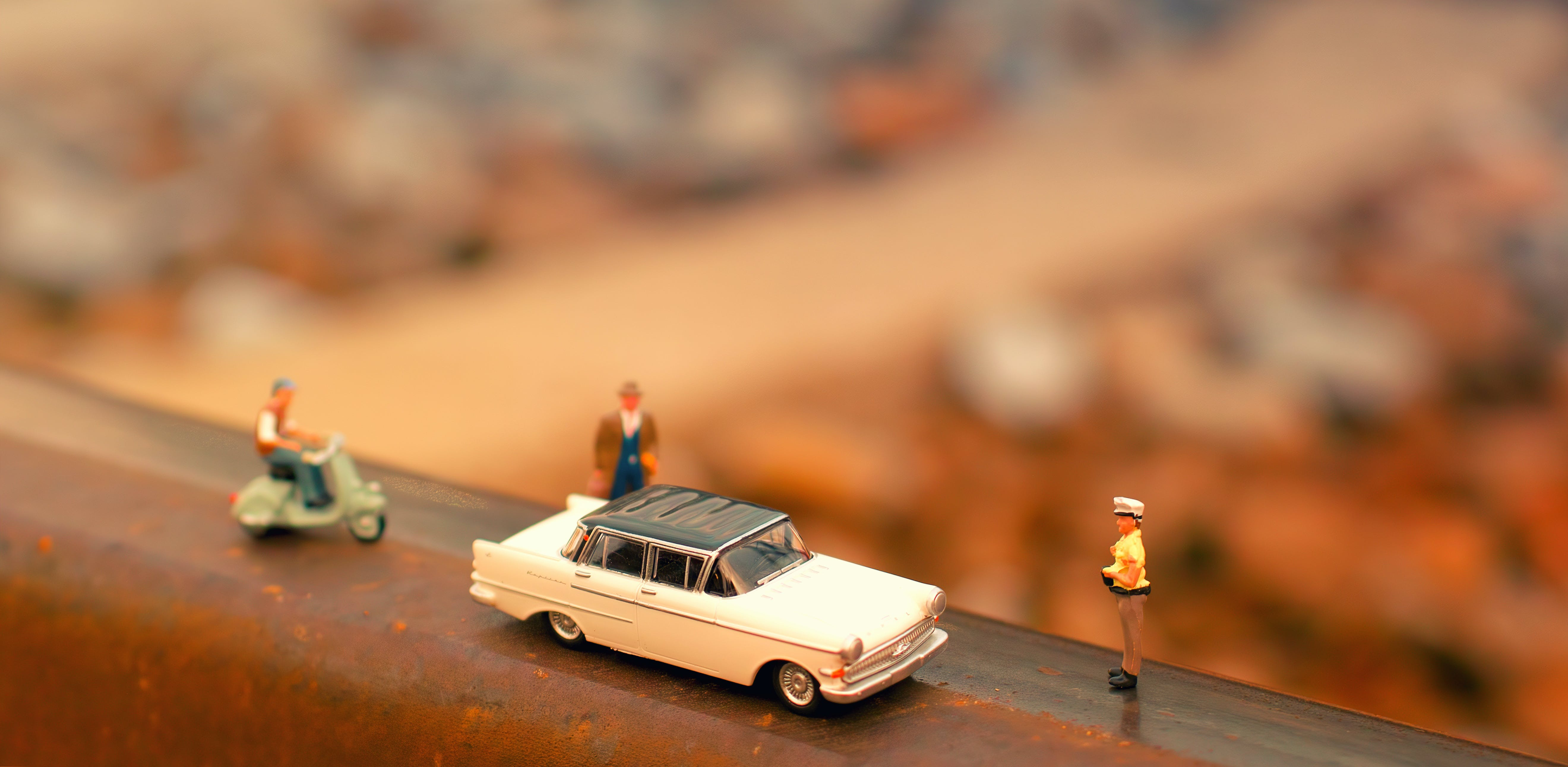 Tilt-shift Photography of Classic Car Scale Model Near Two Figurines