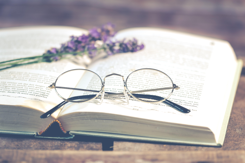 Silver-colored Framed Eyeglasses on Open Book