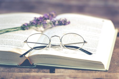 Silver-colored Framed Eyeglasses on Open Book