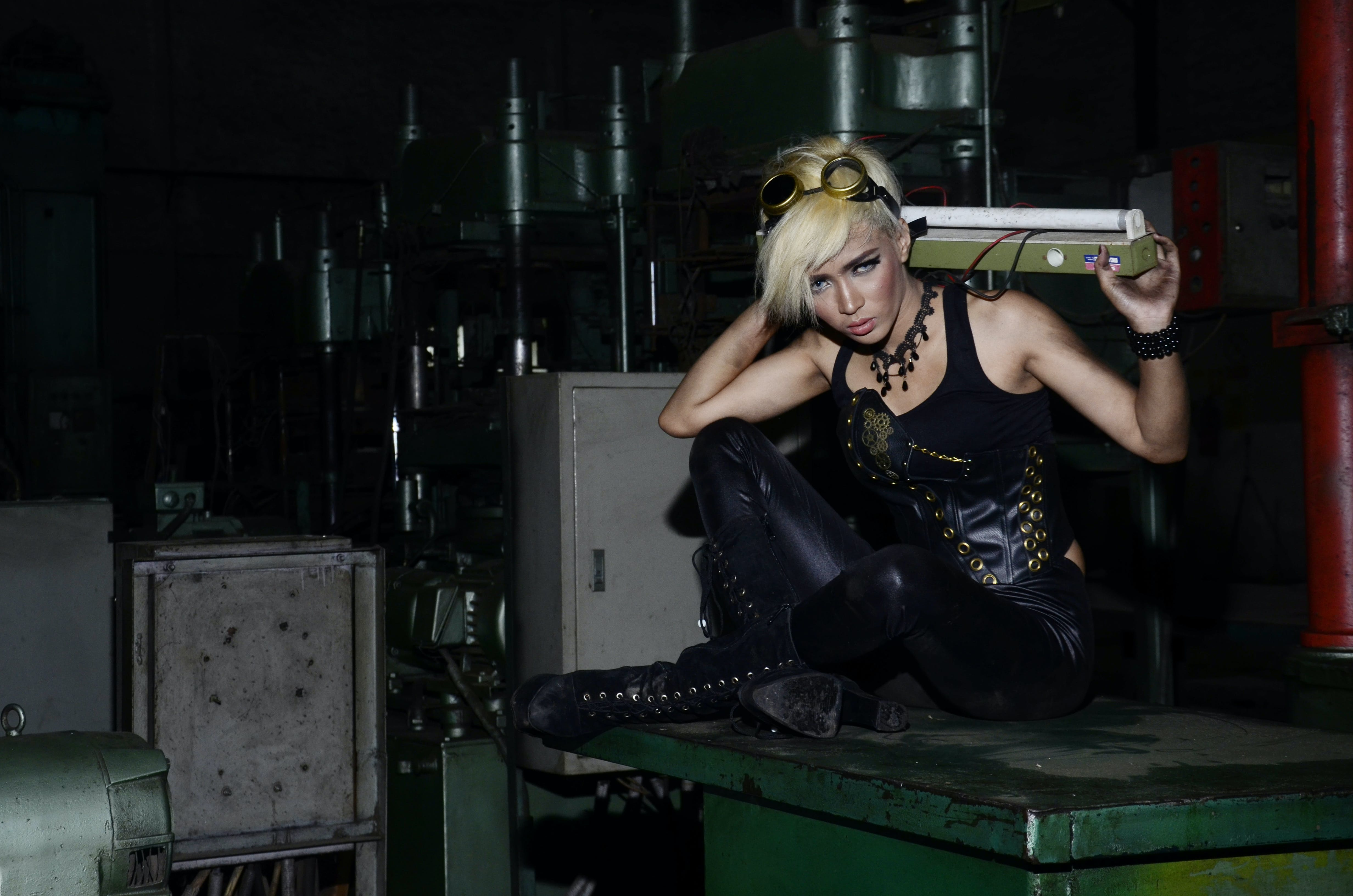 Woman Sitting on Green Metal Industrial Machine