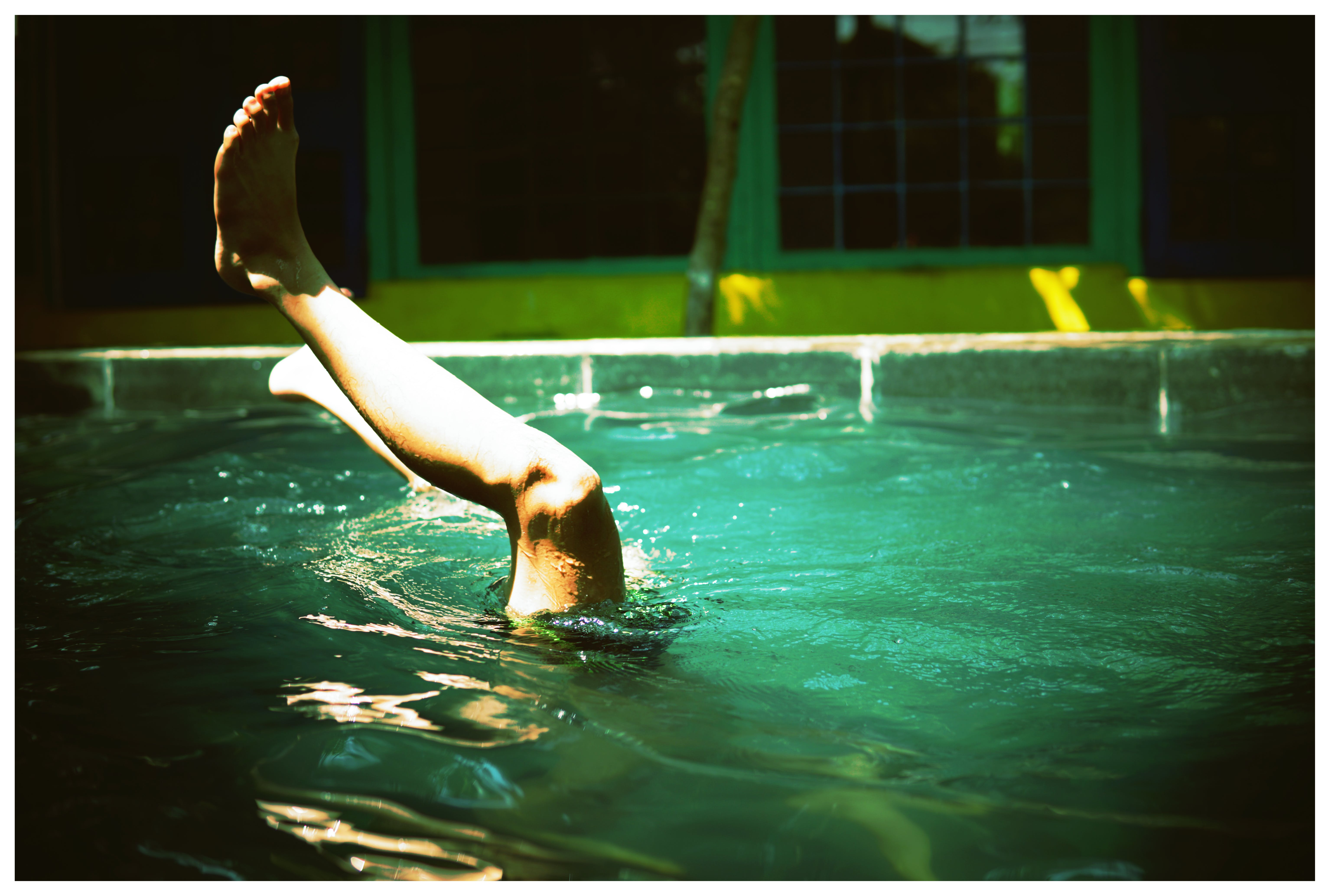 Person Swimming on Pool With Feet in the Air