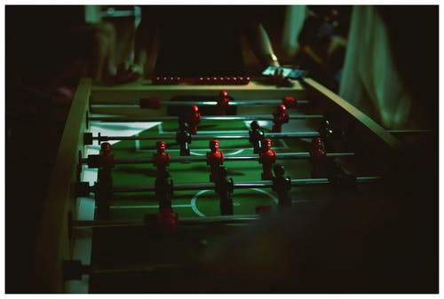 Person Standing Near Foosball Table