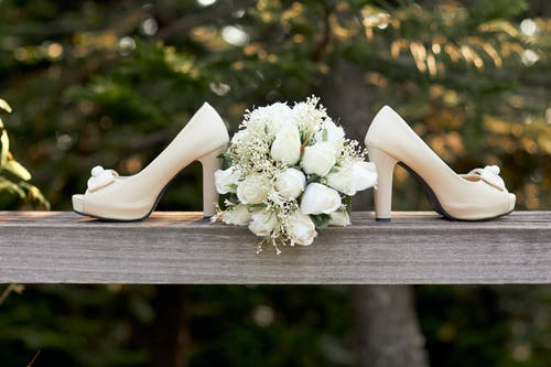 Selective Focus Photography of Pair of White Open-toe Chunky Heeled Shoes and Bouquet Flowers