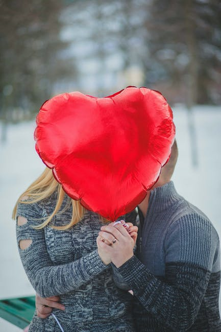 Couple holding hands with red heart balloon