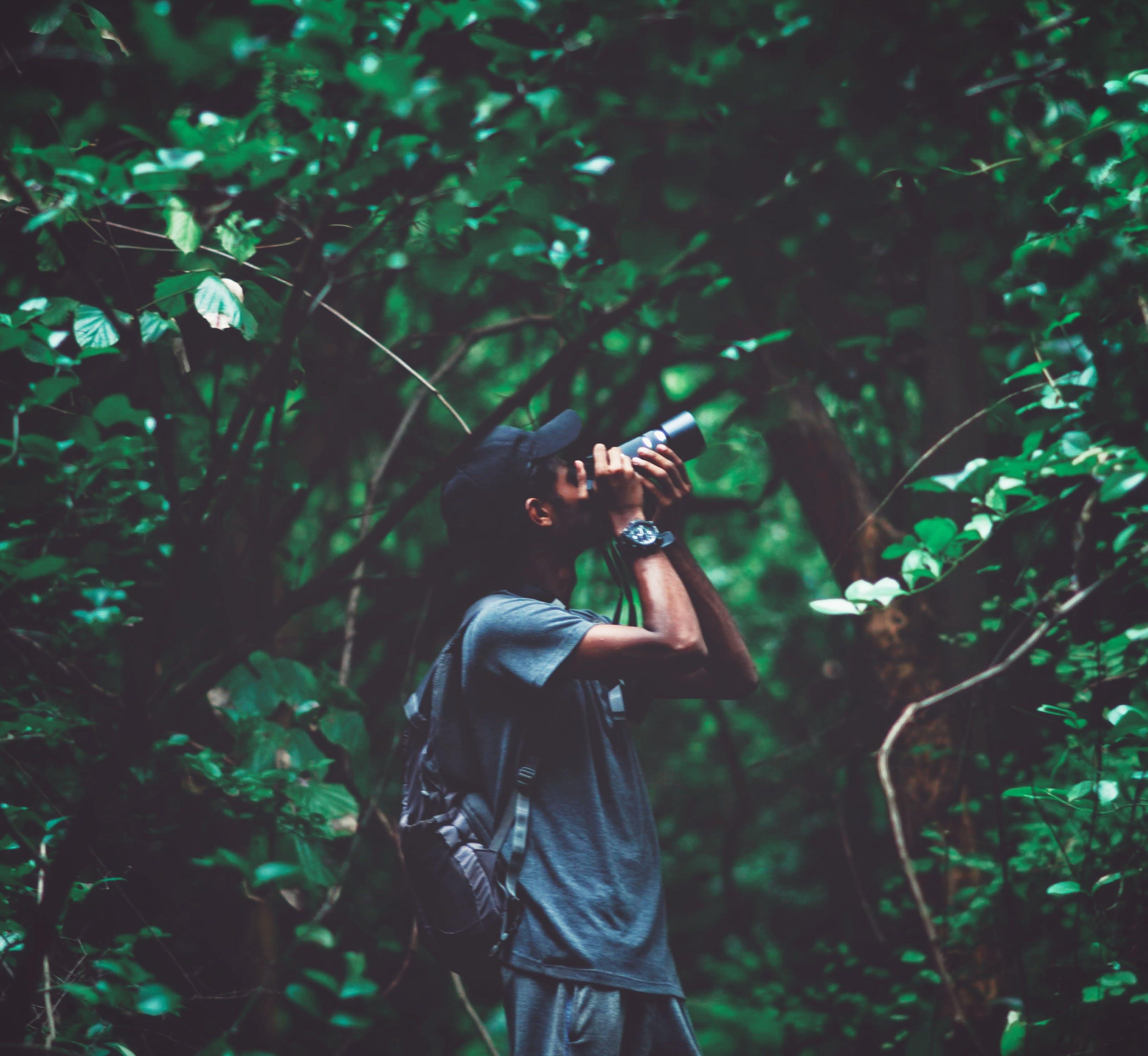 Man Standing Near Tree Taking Photo