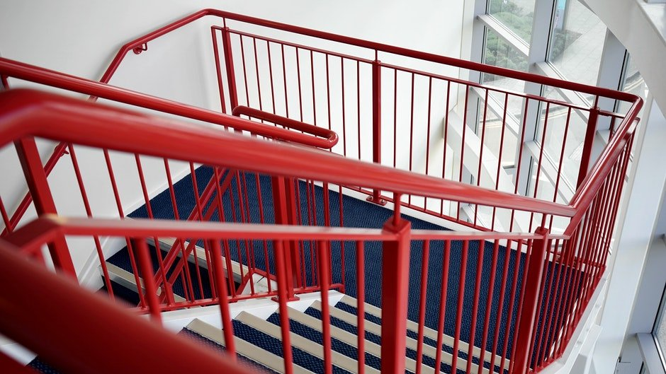 Blue and White Wooden Stairs With Red Metal Handrails