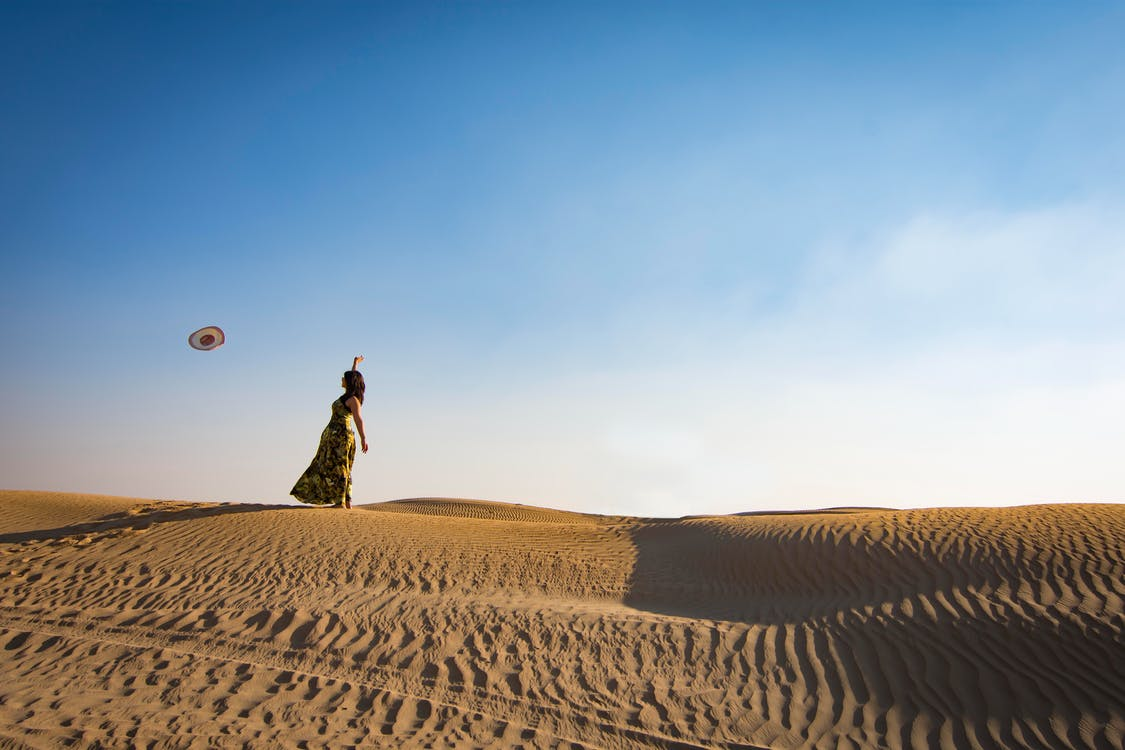 Woman Standing on Sand Dune Throwing Hat