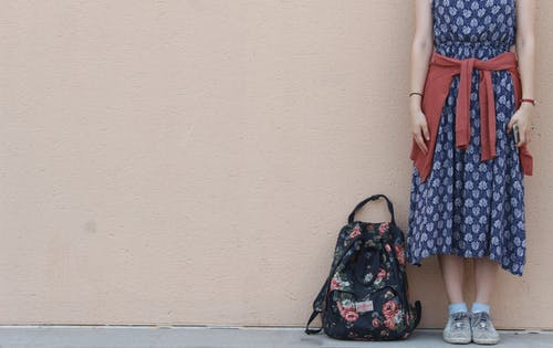 Woman Standing Beside Backpack Near Wall