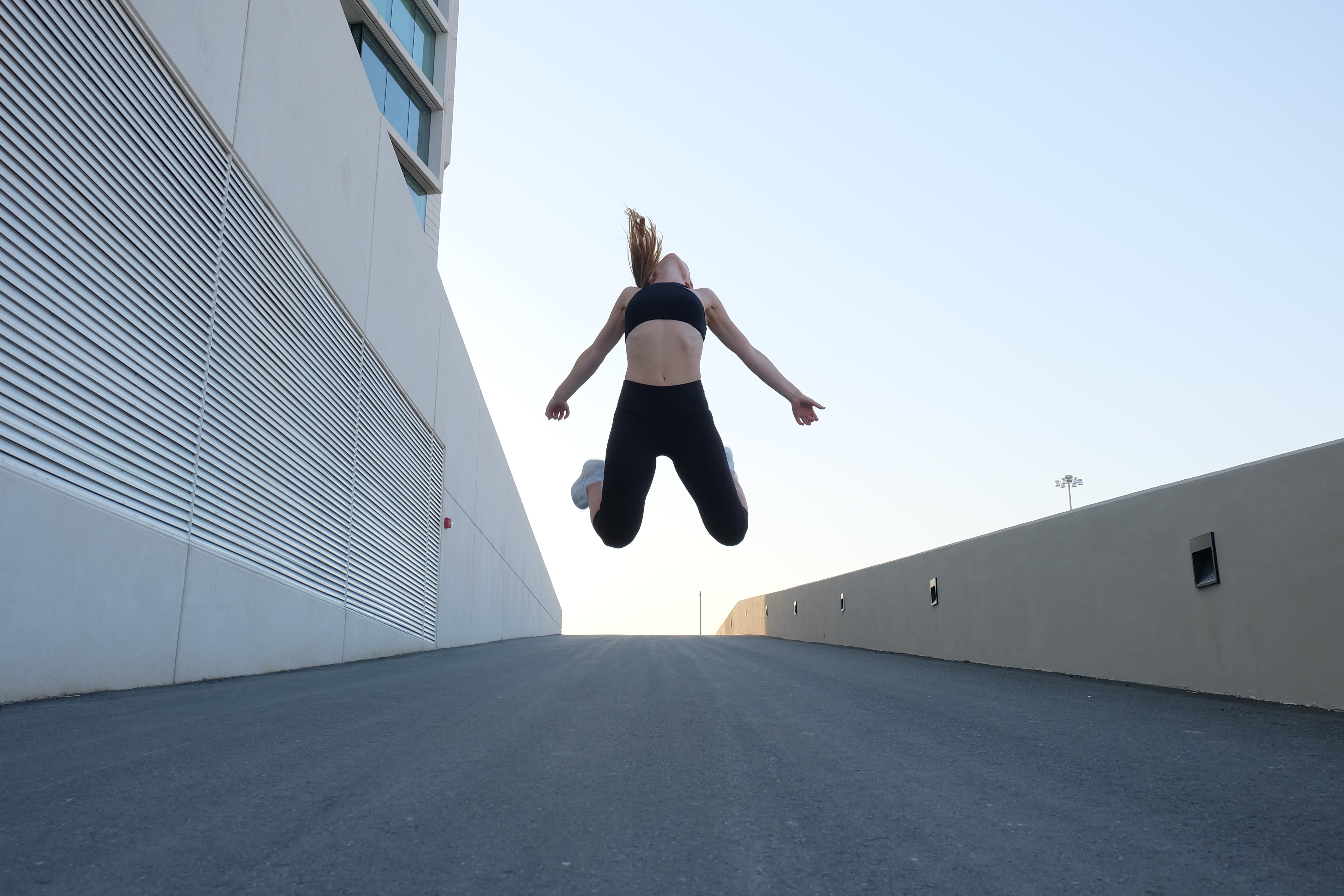 Woman Wearing Black Crop Top Jumping Beside the Building
