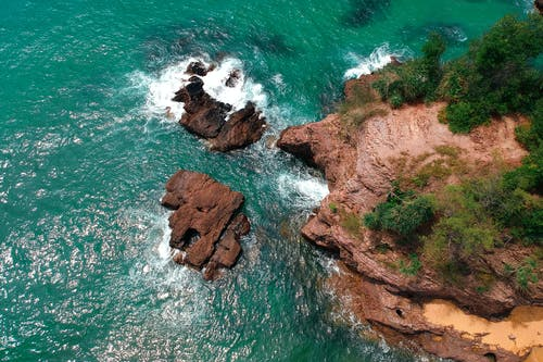 Top View Photo of Rock Formation on Body of Water