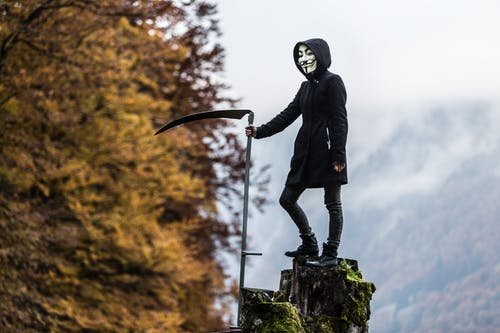 Photo of Person Wearing Guy Fawkes Mask While Holding Scythe