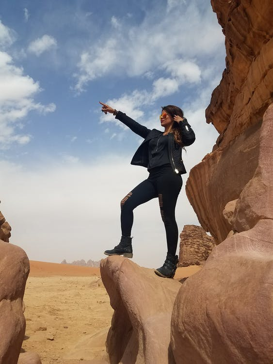 Photo of Woman Standing on Rock Formation