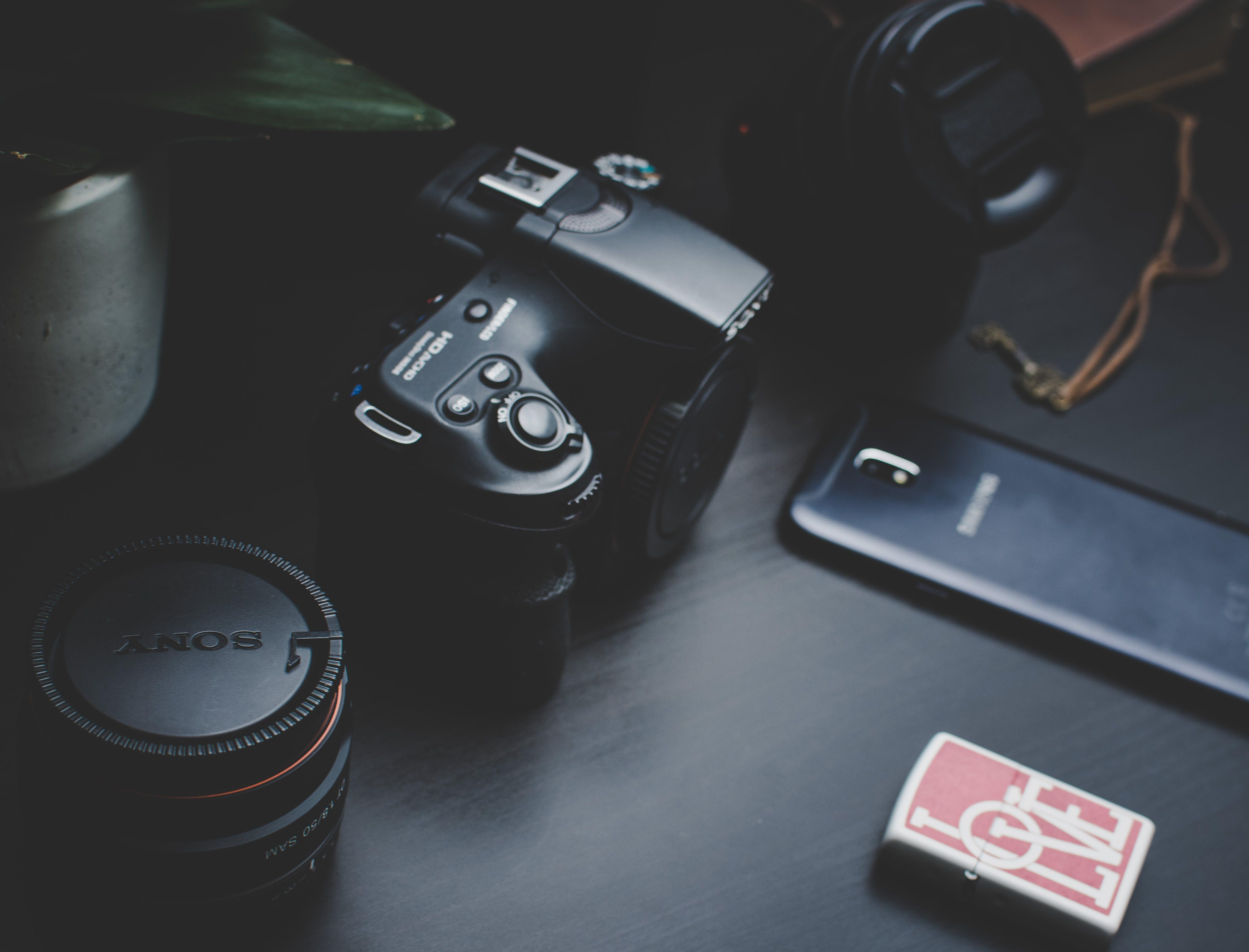Dslr Camera Beside Samsung Smartphone on Black Surface