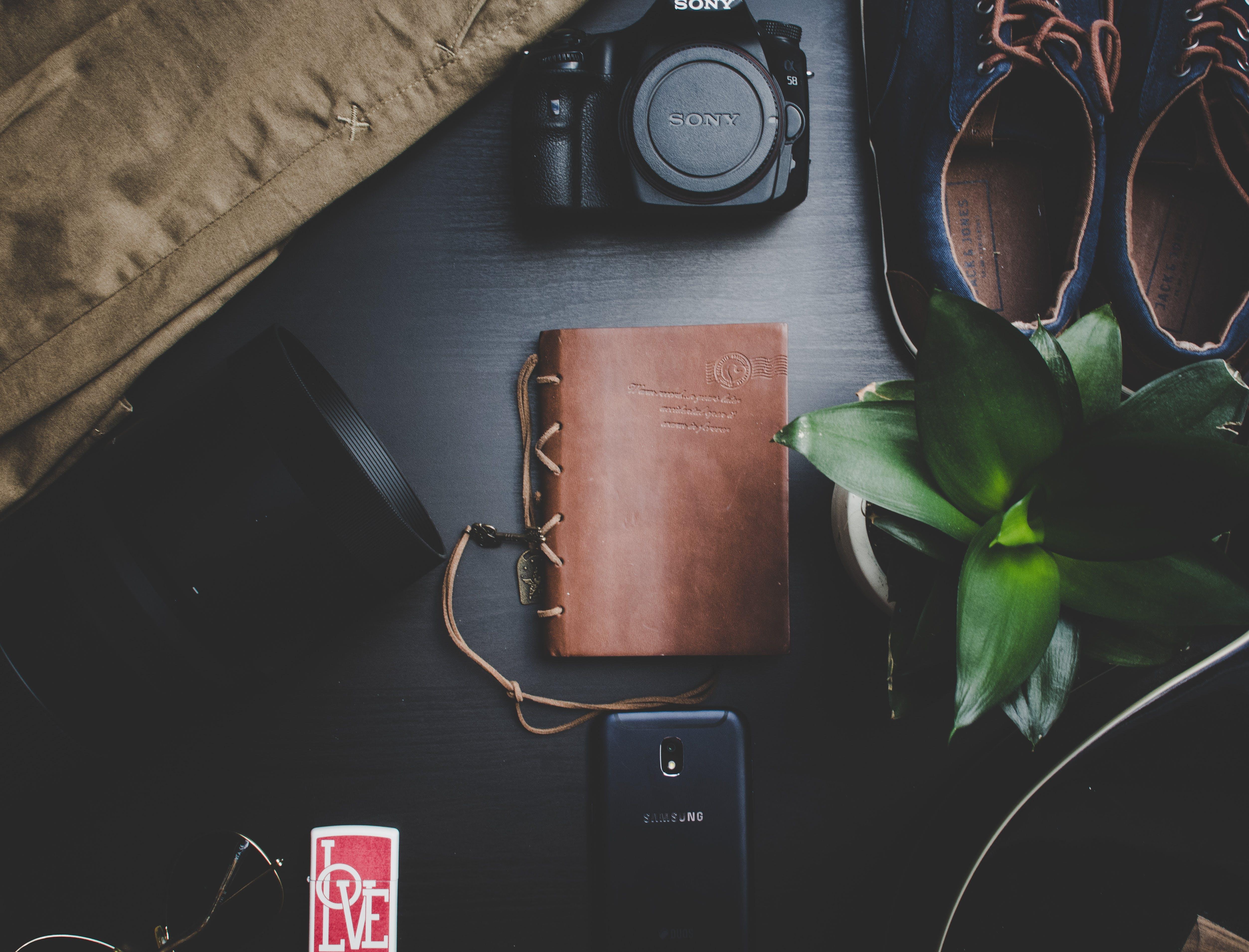 Black Sony Dslr Camera Beside Brown Notebook