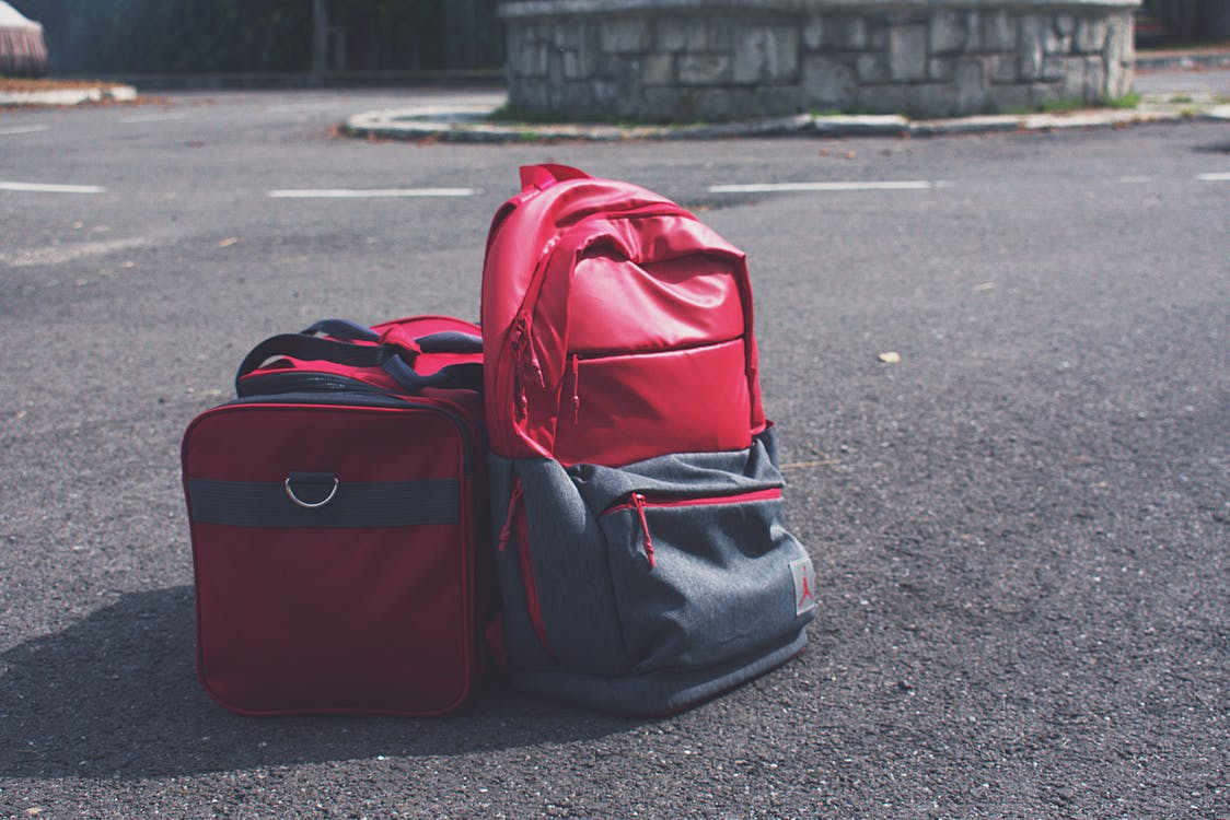Red and Gray Backpack Beside Red Duffel Bag