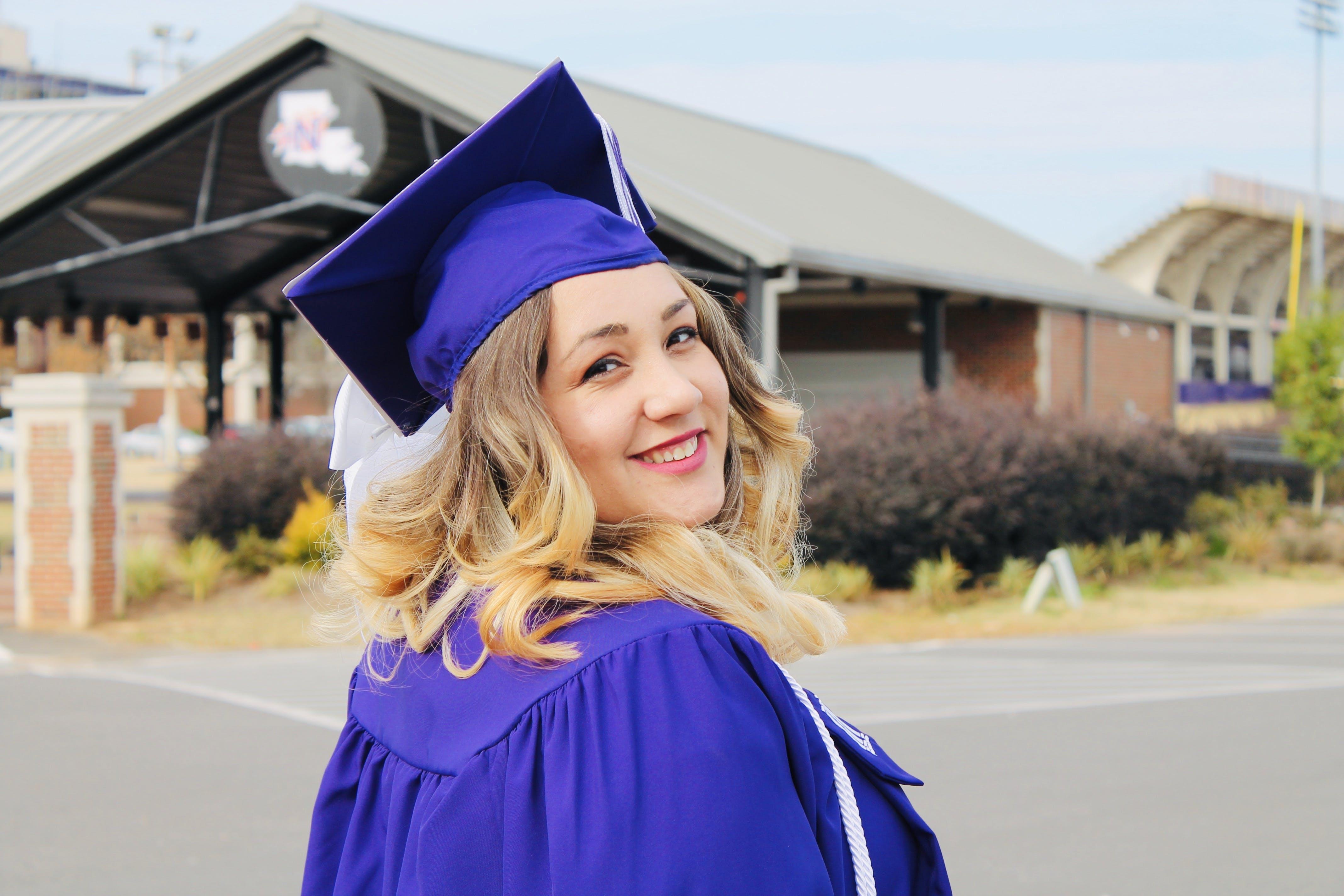 Woman Wearing Purple Mortar Board and Academic Robe