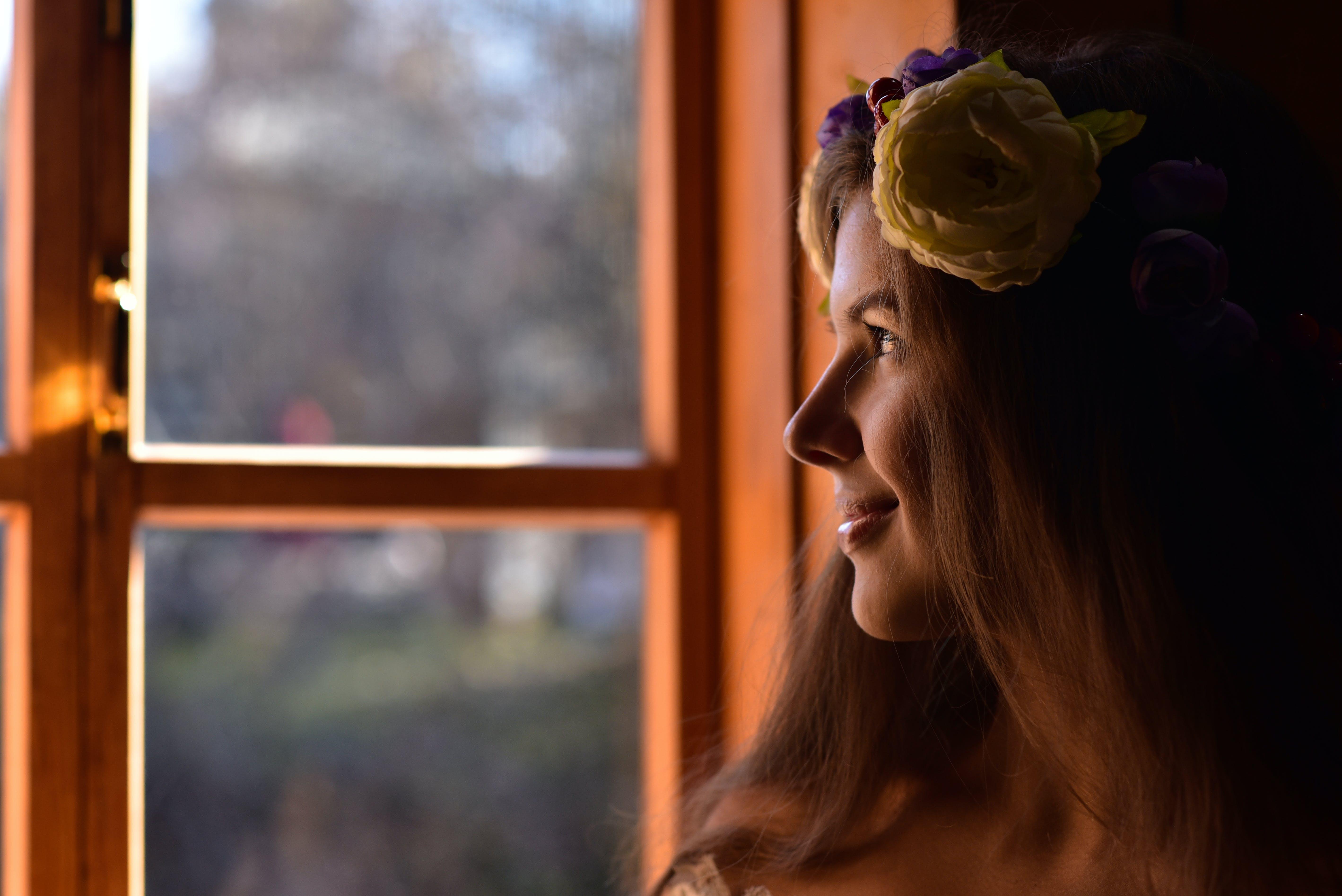 Tilt Shift Lens Photography of Woman Standing Beside Clear Glass Window