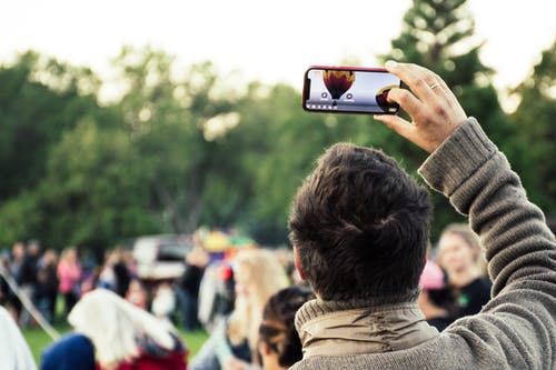 Man Holding Phone Capturing Hot Air Balloon