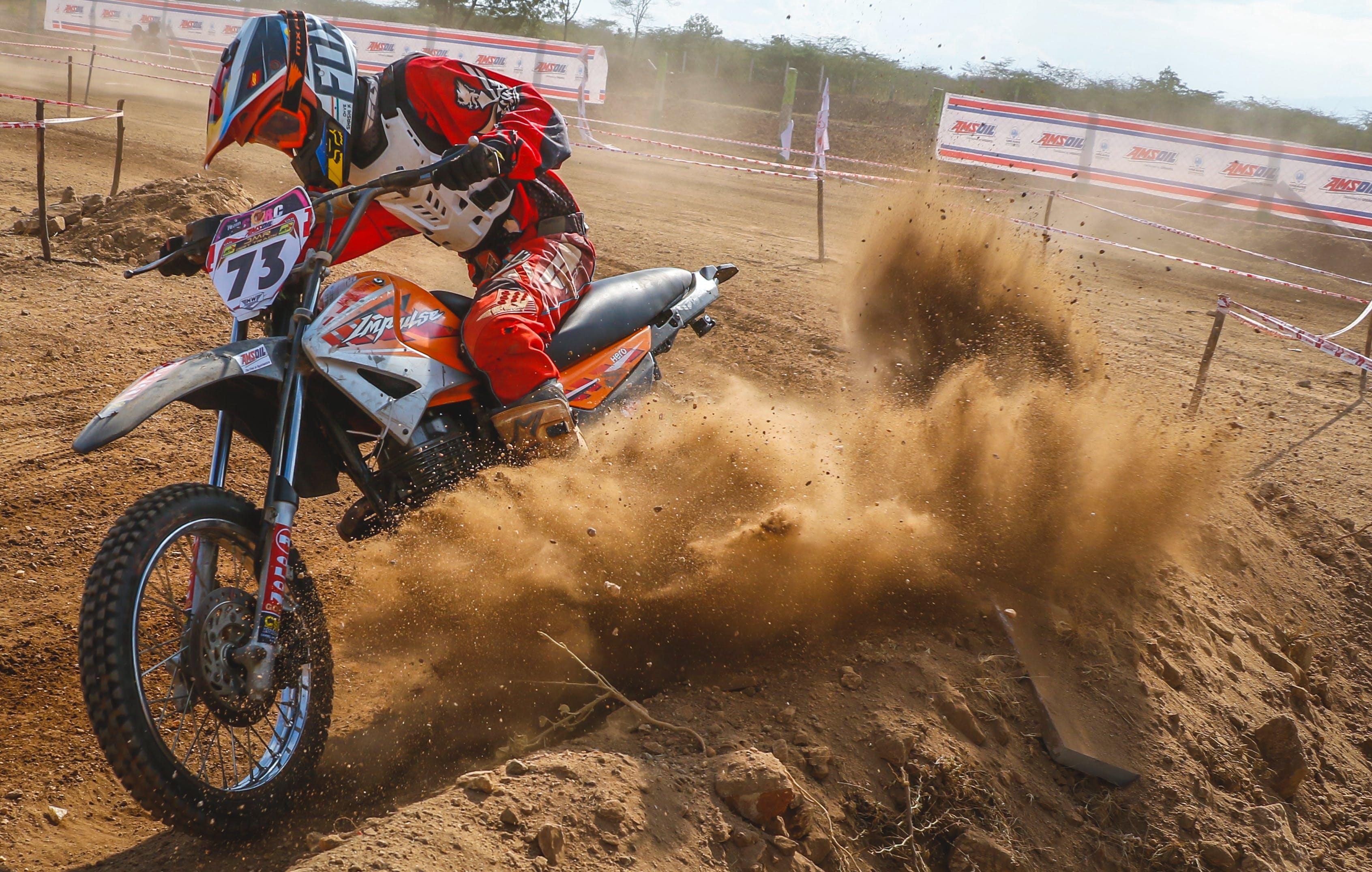Man Riding Motocross Dirt Bike on Dirt Road