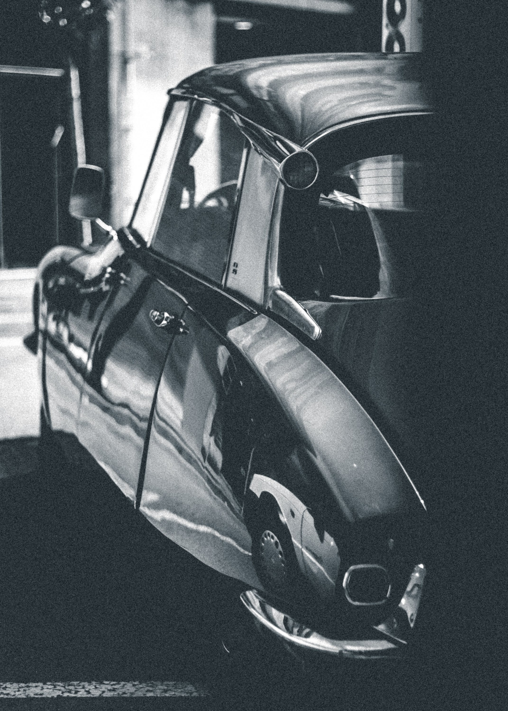 Grayscale Photo of Car Parked Beside Building