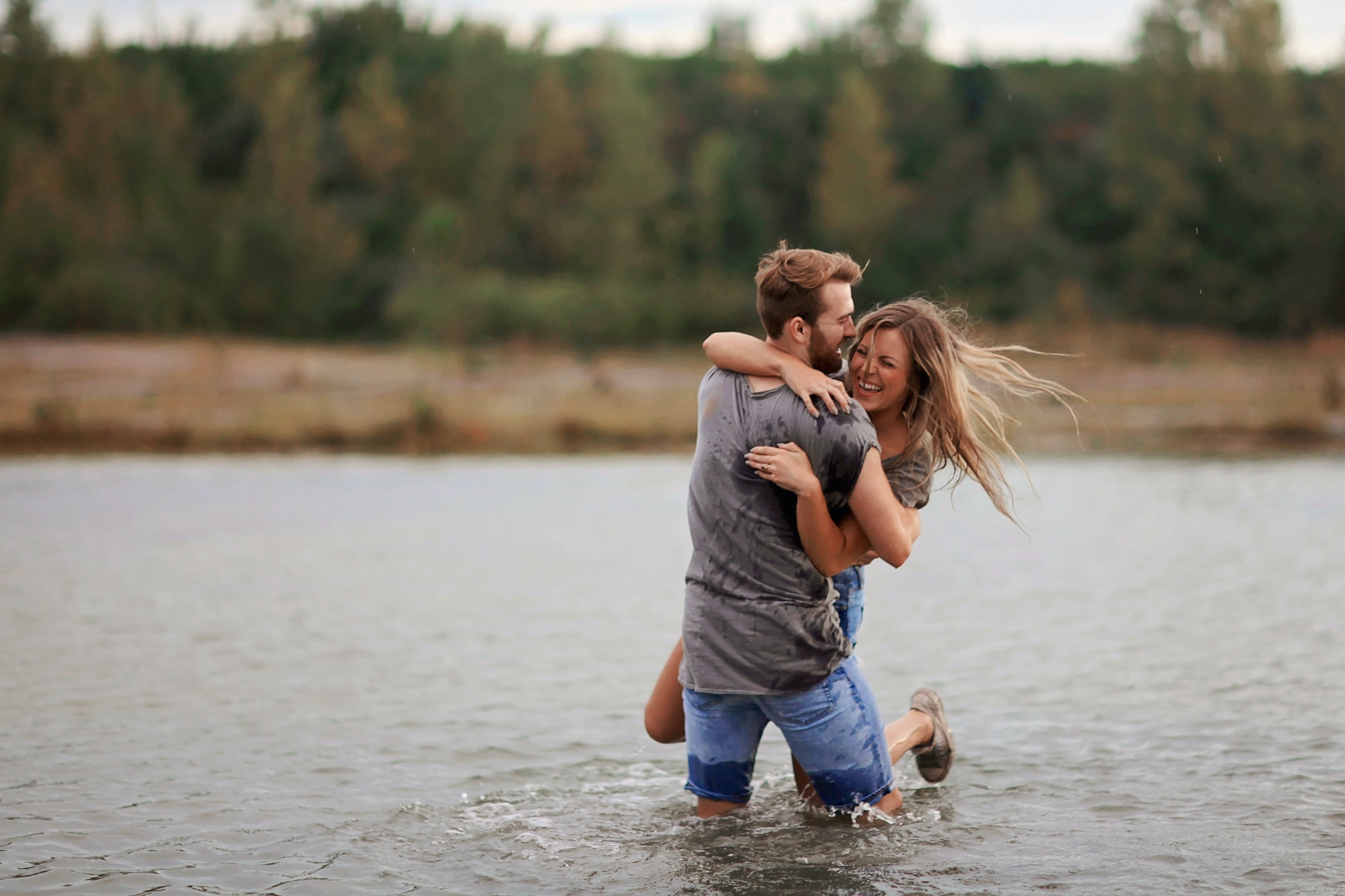 Man Hugging Laughing Woman While Standing in Body of Water