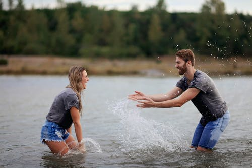 Man and Woman Playing on Body of Water