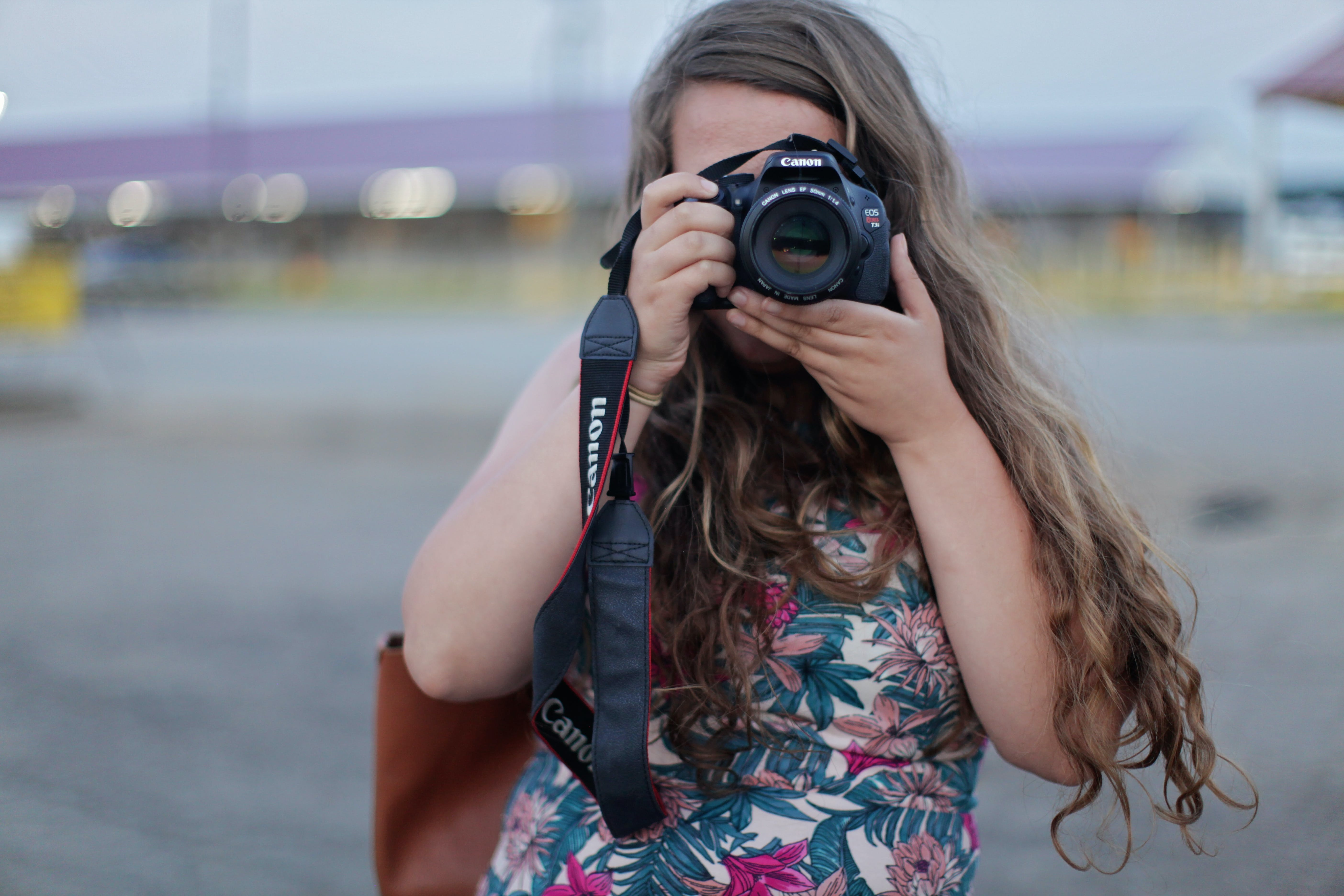 Woman Standing While Holding and Taking Picture from Canon Dslr Camera