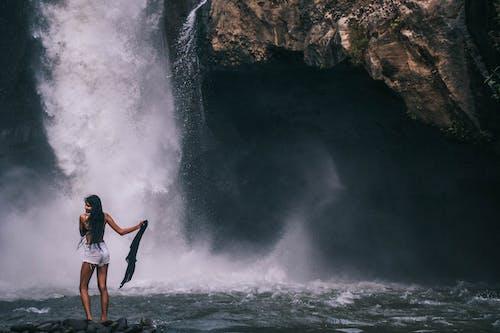 Woman Standing Near Waterfalls