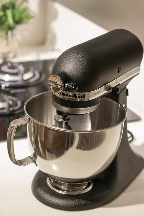 Black and Silver Kitchenaid Stand Mixer on Top of White Surface