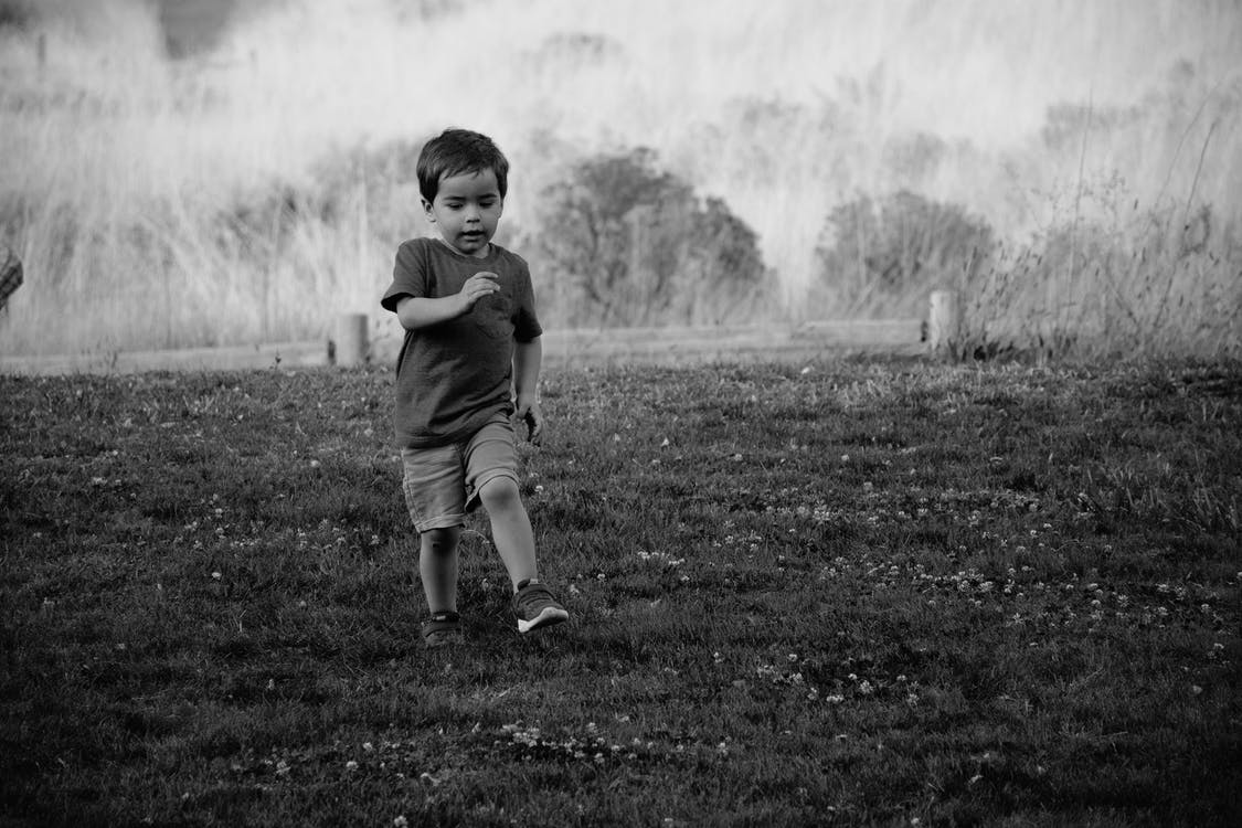 Grayscale Photography of Kid Walking on Grass