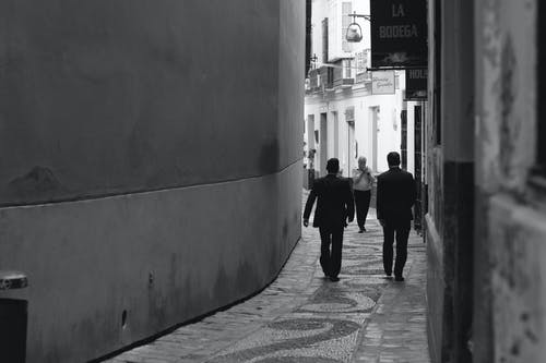 Grayscale Photo of Men Walking Near Wall