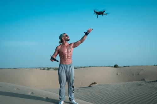 Man Playing Quadcopter on Desert