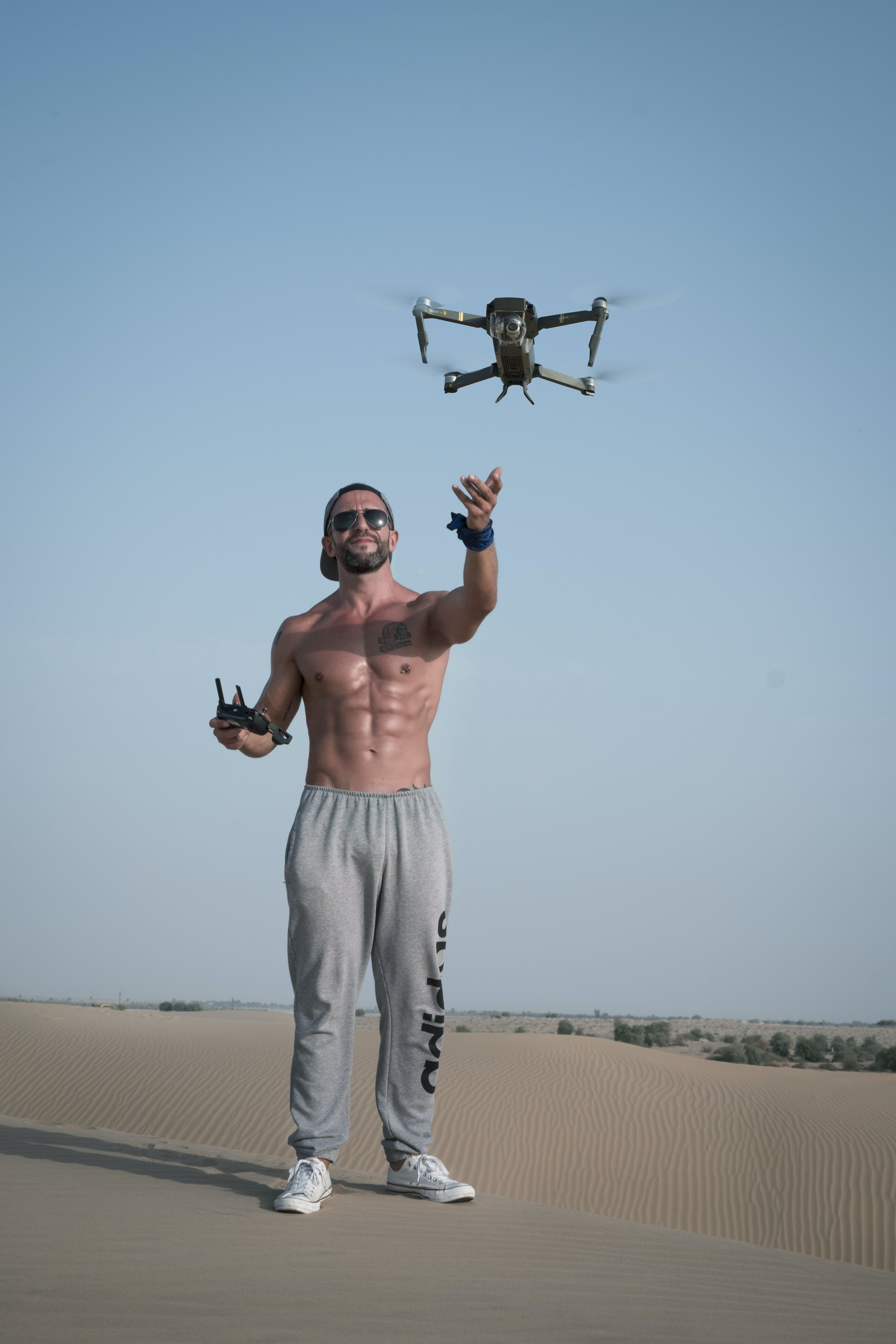 Man Holding Drone Remote Standing on Gray Concrete Pavement
