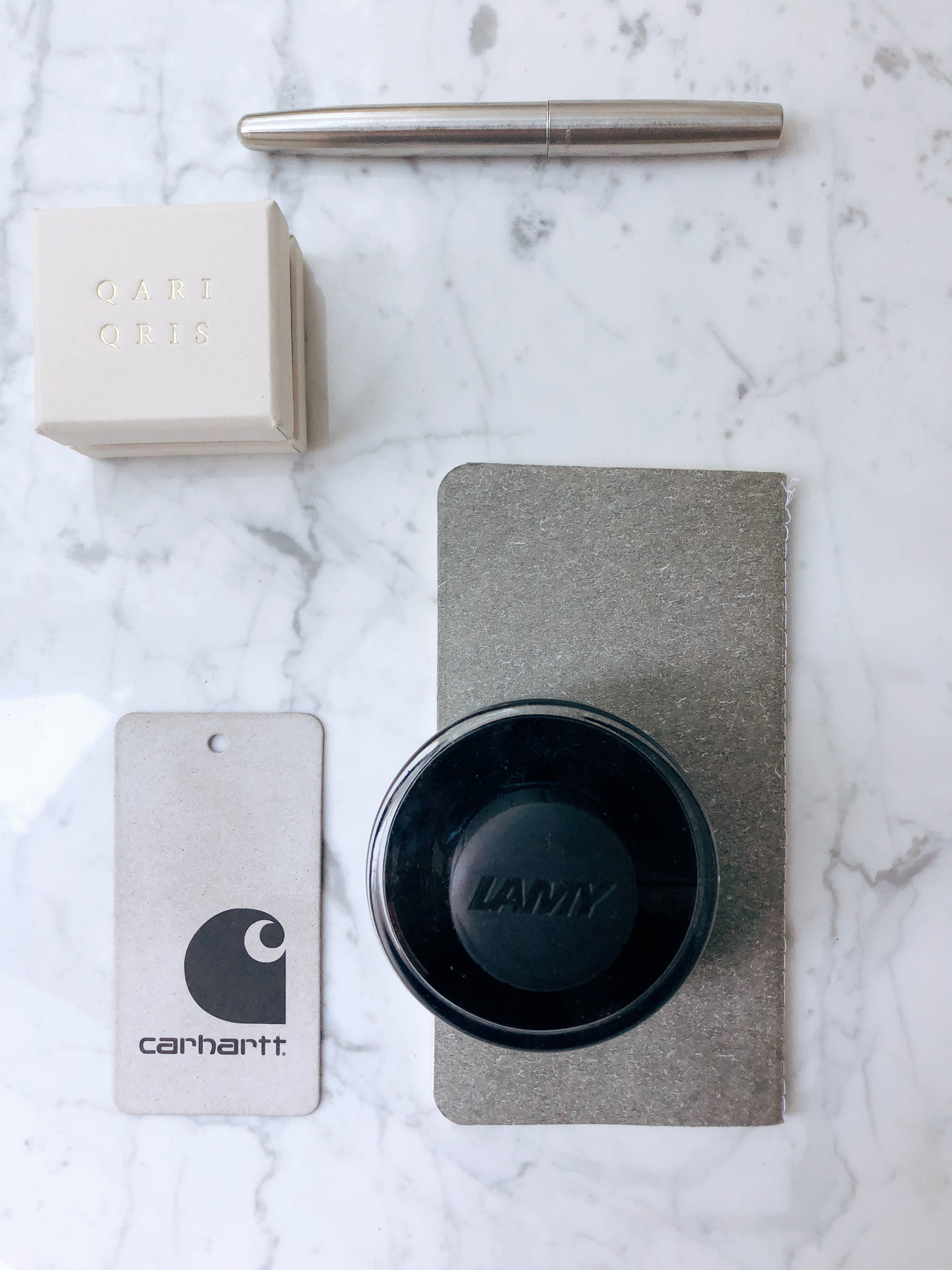 Carhartt Price Tag Beside Lamy Container on Marble Slab